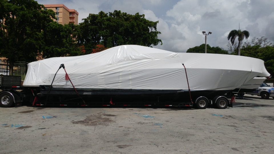 Full length picture of the Sundancer from the right side. It is fully shrink wrapped and secured to the trailer.